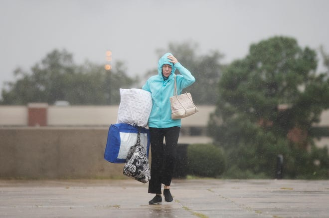 A woman makes her way on Oct.10, 2018 to an evacuation shelter at the Donald L. Tucker Civic Center on the Florida State University campus in Tallahassee. Hurricane Michael has forced thousands of residents to flee their homes.