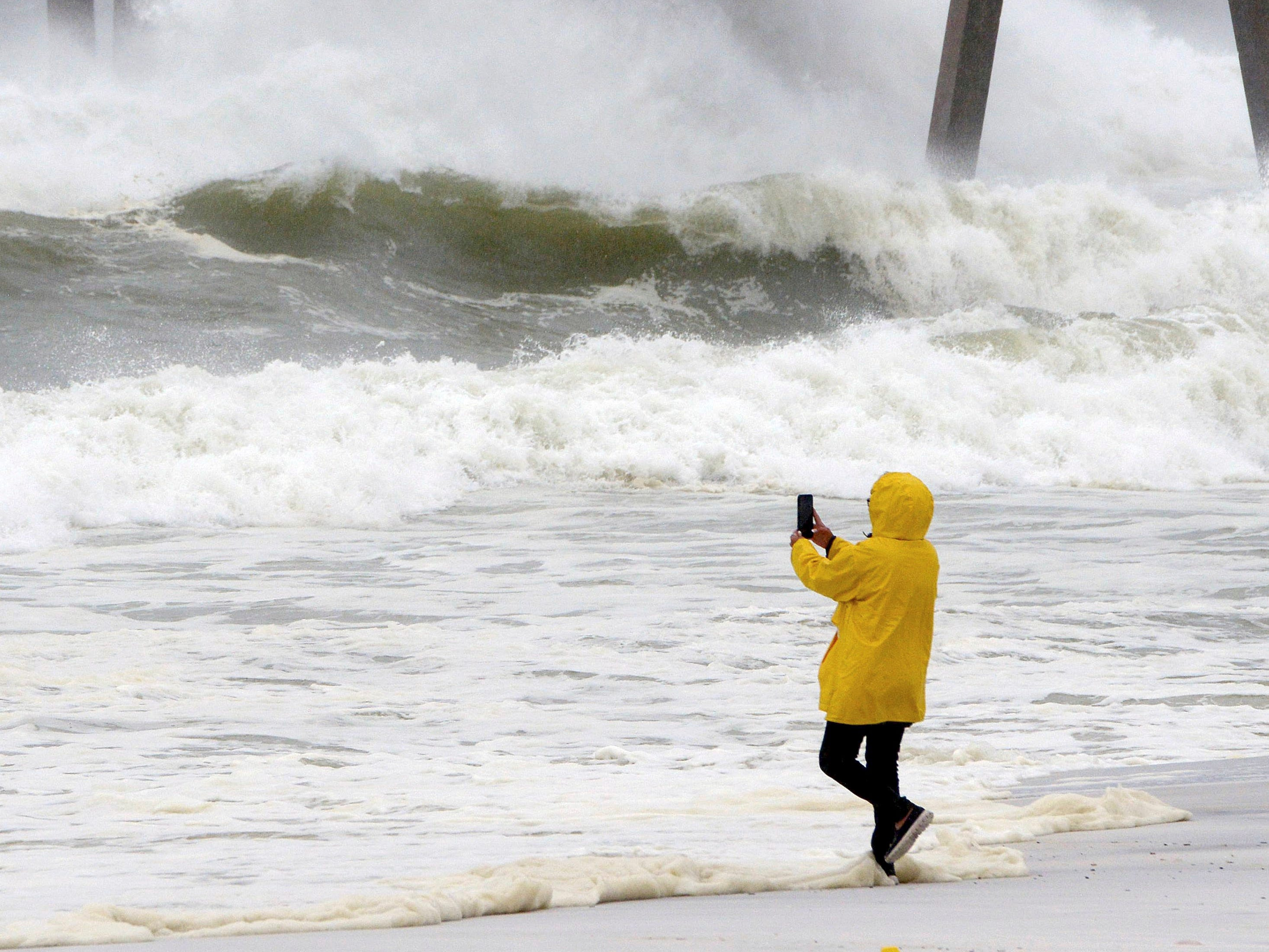 A beachgoer take photos of the waves on Wednesday Oct. 10, 2018, on Okaloosa Island in Fort Walton Beach, Fla., behind the boardwalk as Hurricane Michael impacts the coast. (Nick Tomecek/Northwest Florida Daily News via AP) ORG XMIT: FLPLA104
