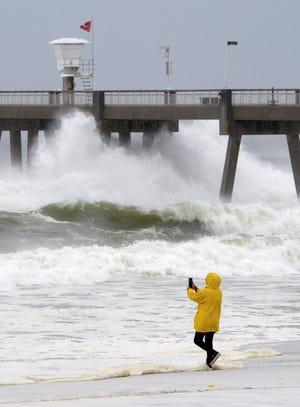 A beachgoer take photos of the waves on Wednesday Oct. 10, 2018, on Okaloosa Island in Fort Walton Beach, Fla., behind the boardwalk as Hurricane Michael impacts the coast. (Nick Tomecek/Northwest Florida Daily News via AP) ORG XMIT: FLPLA104