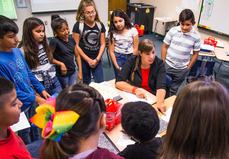 Rebecca Garelli , sitting, helps her sixth-grade class at Sevilla West Elementary School in Phoenix.