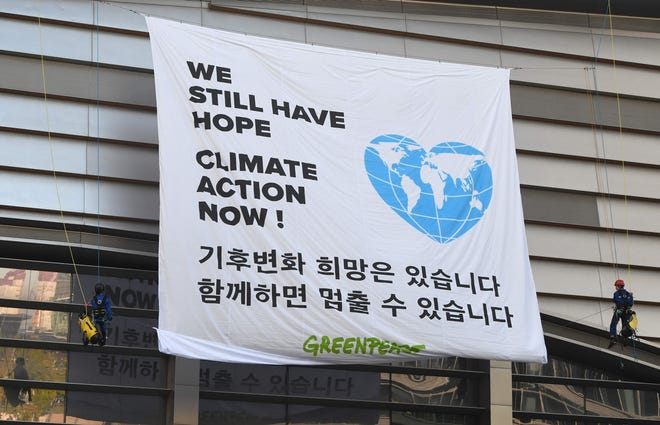 Greenpeace activists display a banner outside a conference of the Intergovernmental Panel for Climate Change in Incheon, South Korea, on Oct. 8, 2018.