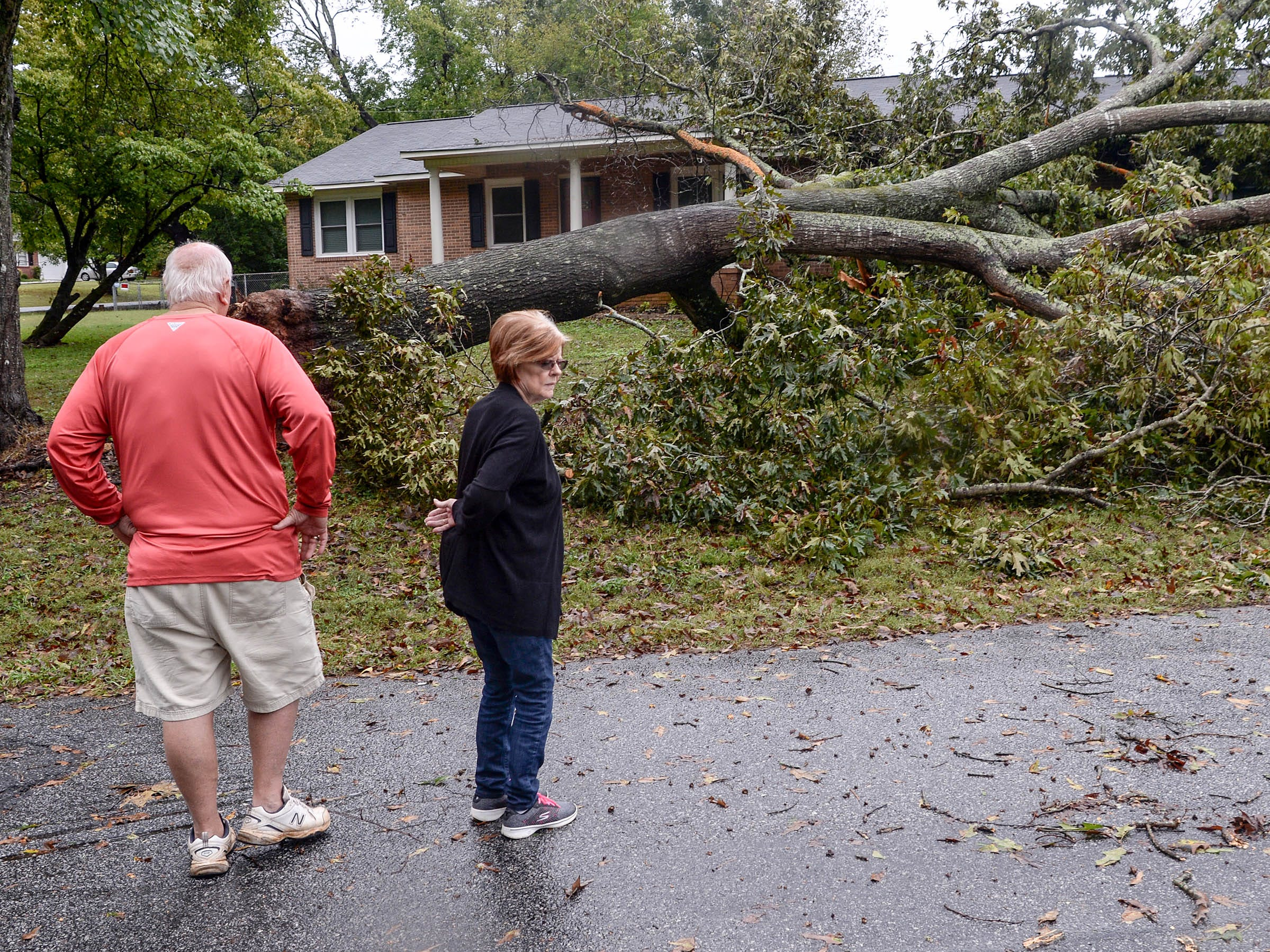 Ray and Joy Browning of Anderson look at a 60-year old oak tree which grazed the home of their son Adam Browning before sunrise, sparing the bedrooms. Rainfall from Hurricane Michael came through Anderson County on Thursday morning.
