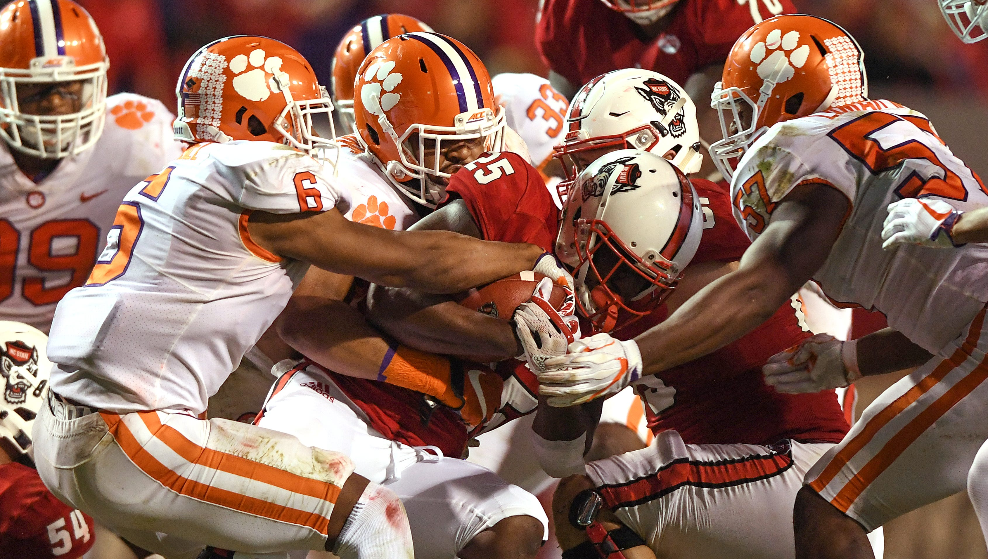 NC State running back Reggie Gallaspy II (25) is stopped by Clemson's defense during the 4th quarter on Saturday, November 4, 2017 at N.C. State's Carter Finley Stadium in Raleigh, N.C.