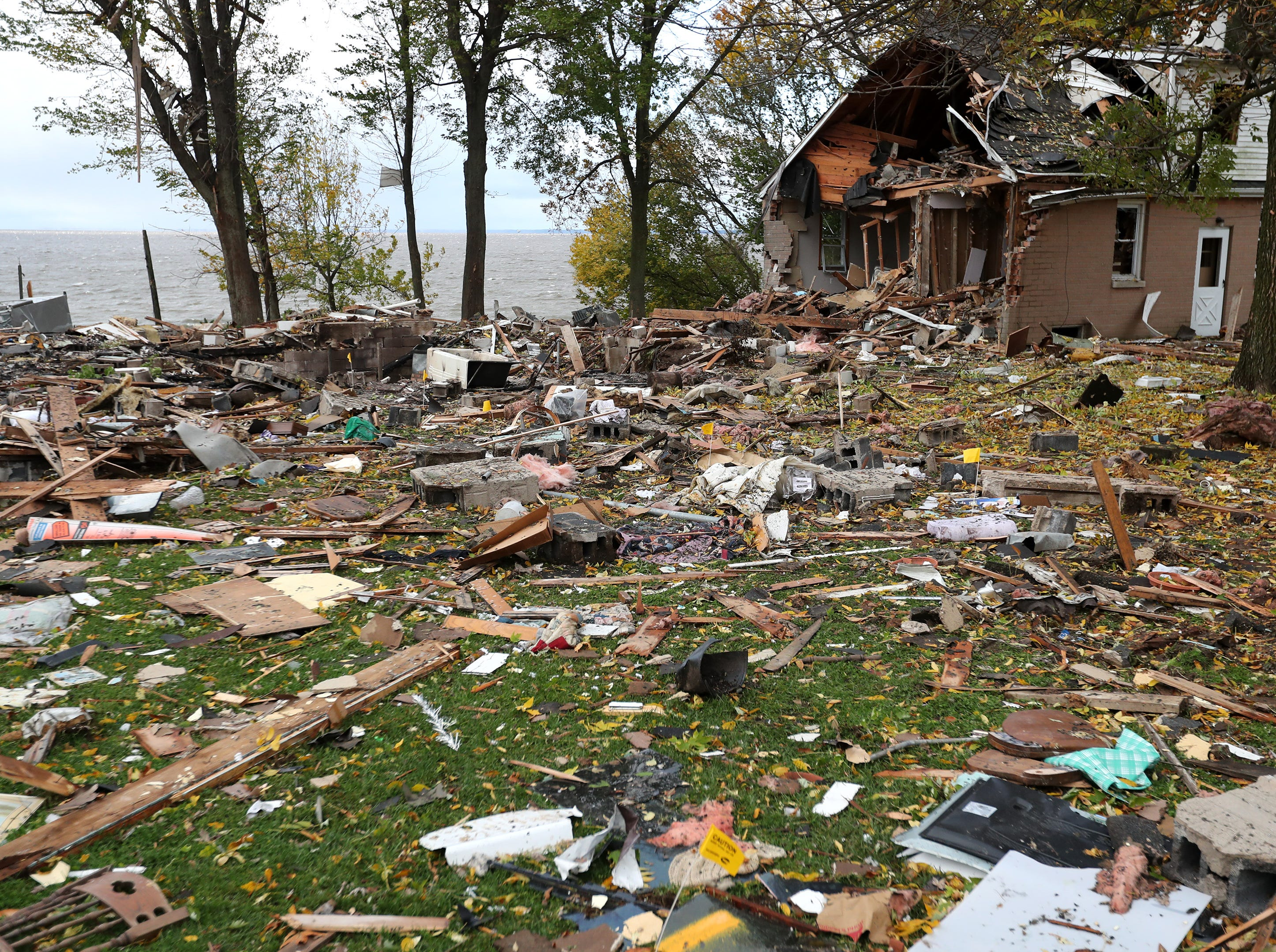 The scene of a house explosion that completely destroyed one home (left) and left neighboring properties damaged (right ) Thursday, Oct. 11, 2018, in Harrison, Wis.