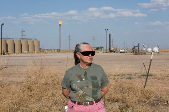 Suzanne Franklin stands near her home in Reeves County, West Texas, on April 11, 2018. Some mornings Franklin wakes with a nose full of dried blood, her voice filled with gravel. Her husband Jim suffers from respiratory problems, too. Complaints like hers are common among people who live near gas sites, academic research has found. Flares burning off gas spew pollutants that assault the respiratory system. (Marjorie Kamys Cotera/The Texas Tribune via AP)