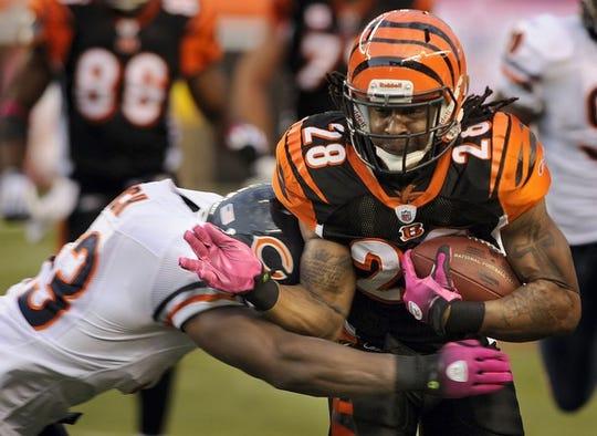 Cincinnati Bengals running back Bernard Scott, right, tries to evade a Chicago Bears tackler during a 2009 game in Cincinnati.