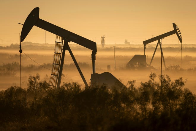 Fog blankets a low-lying area where pumpjacks operate in West Texas, northeast of Kermit, on Sept. 12, 2018. In December 2017, companies in the Permian Basin - an ancient, oil-rich seabed that spans West Texas and southeastern New Mexico - produced twice as much oil as they had four years earlier, during the last boom. Forecasters expect production to double again by 2023. (Jerod Foster/The Texas Tribune via AP)