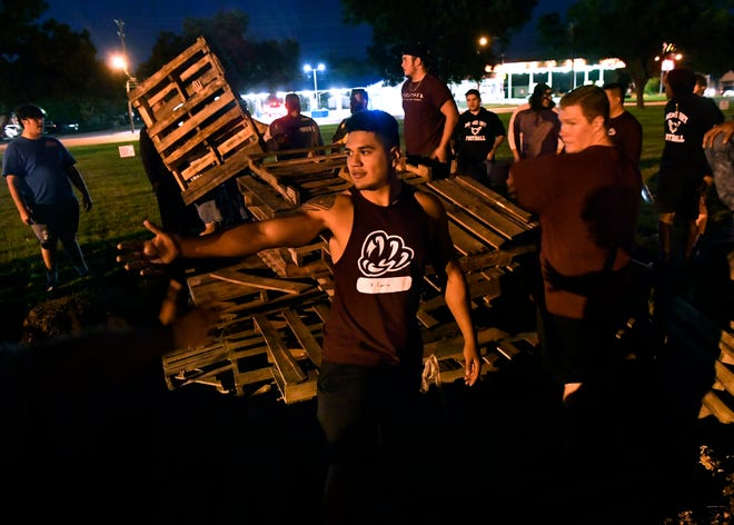 Francisco Garcia gestures for another wooden pallet as he and other McMurry University students build the homecoming bonfire Wednesday evening. All three universities are holding homecoming activities this weekend.