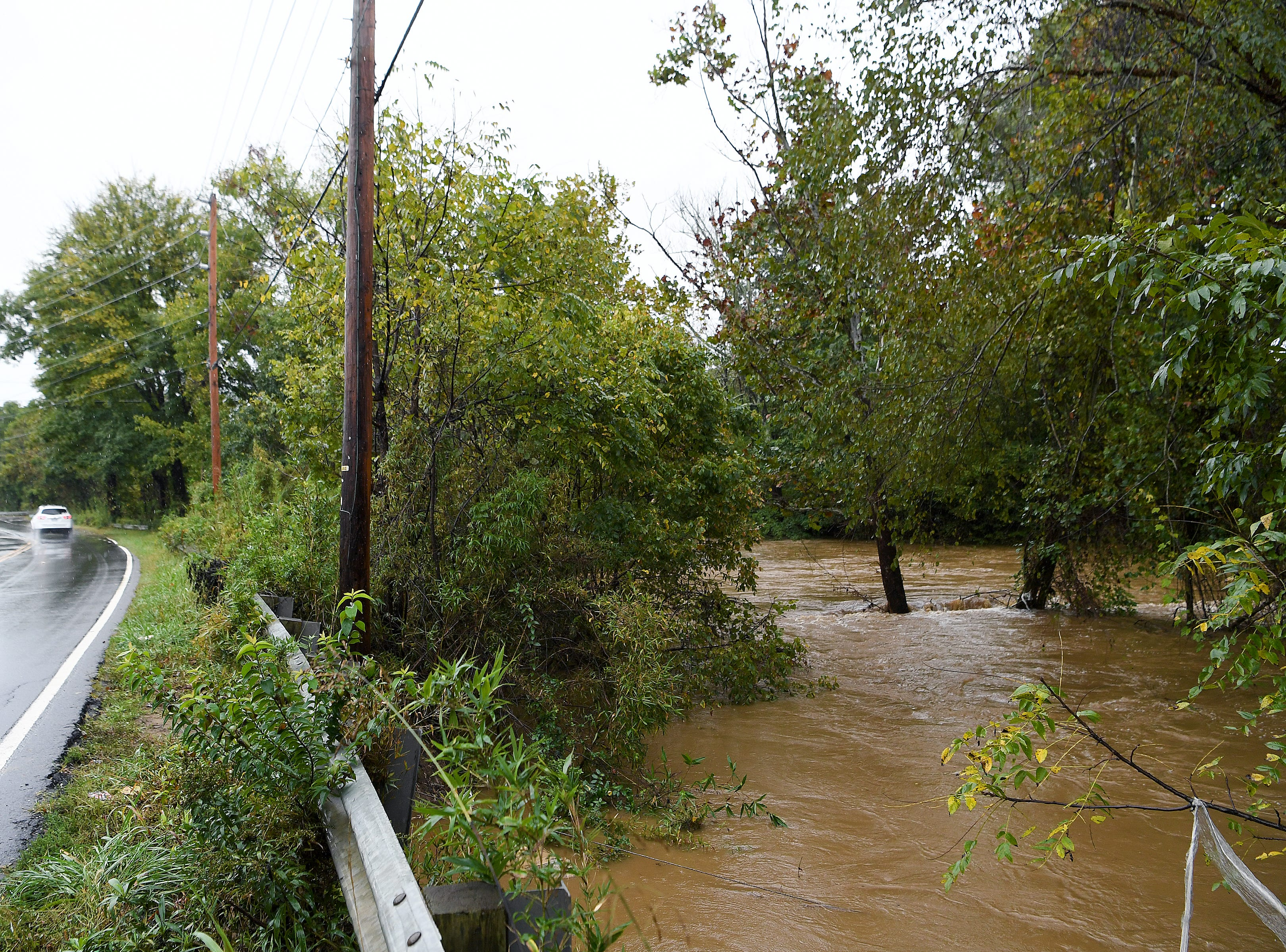 The Swannanoa River swells toward Swannanoa River Road as traffic is allowed to pass following a water rescue by the Asheville Fire Department of two people trapped in a hammock by flood water at a makeshift camp on Oct. 11, 2018.