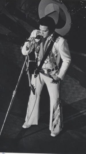 Elvis Presley on stage in Asheville in July 1975. The King of Rock n' Roll gave a customized acoustic guitar to Asheville resident Mike Harris during a show. Harris sold the guitar at auction in 2016.