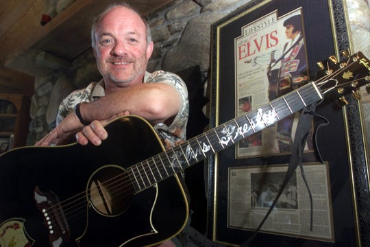 In this file photo, Mike Harris sits in his living room with the guitar Elvis Presley guitar the King gave him during a July 1975 concert at the Asheville Civic Center. Harris put the guitar up for sale, and it sold at auction in May 2016 for $334,000