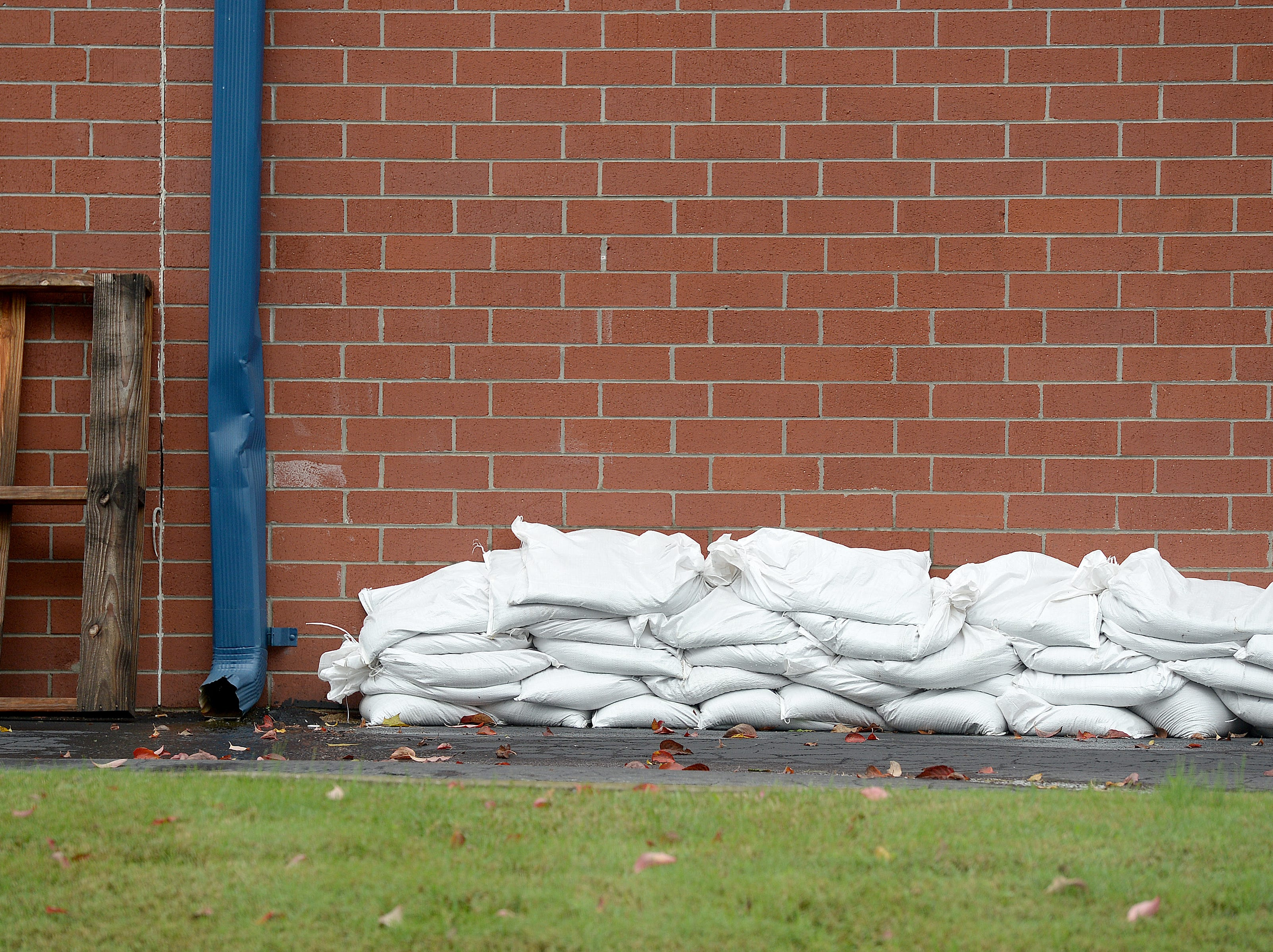 Sandbags are piled behind a FedEx Store on Swannanoa River Road on Oct. 11, 2018.