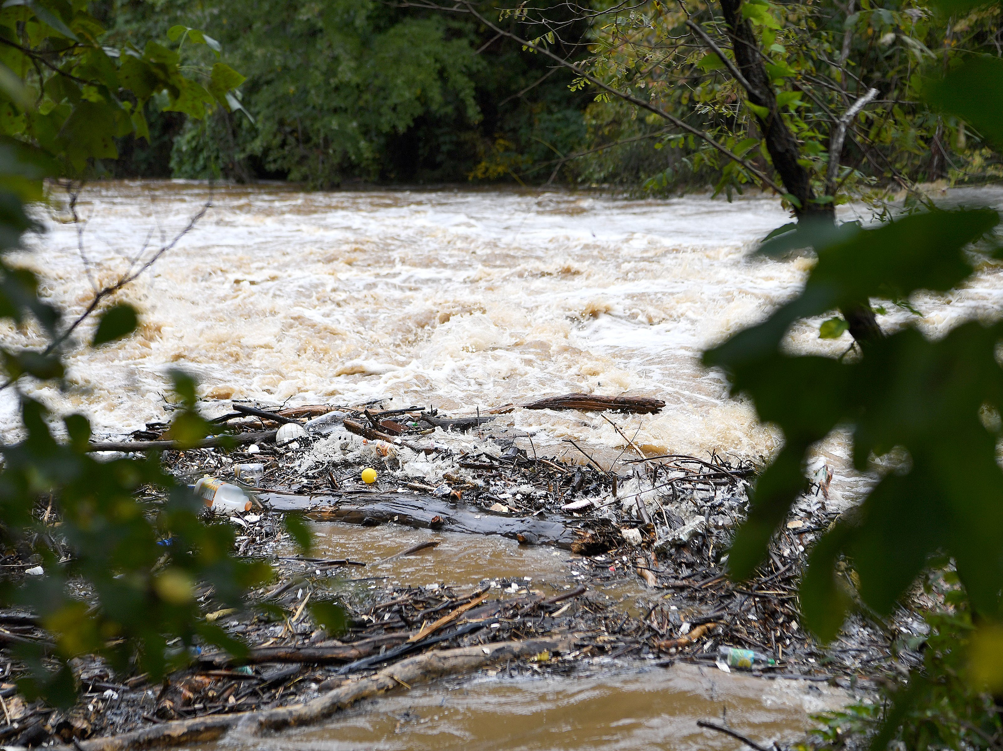 Trash floats on top of the Swannanoa River at Recreation Park as the area floods due to rains from Hurricane Michael on Oct. 11, 2018.