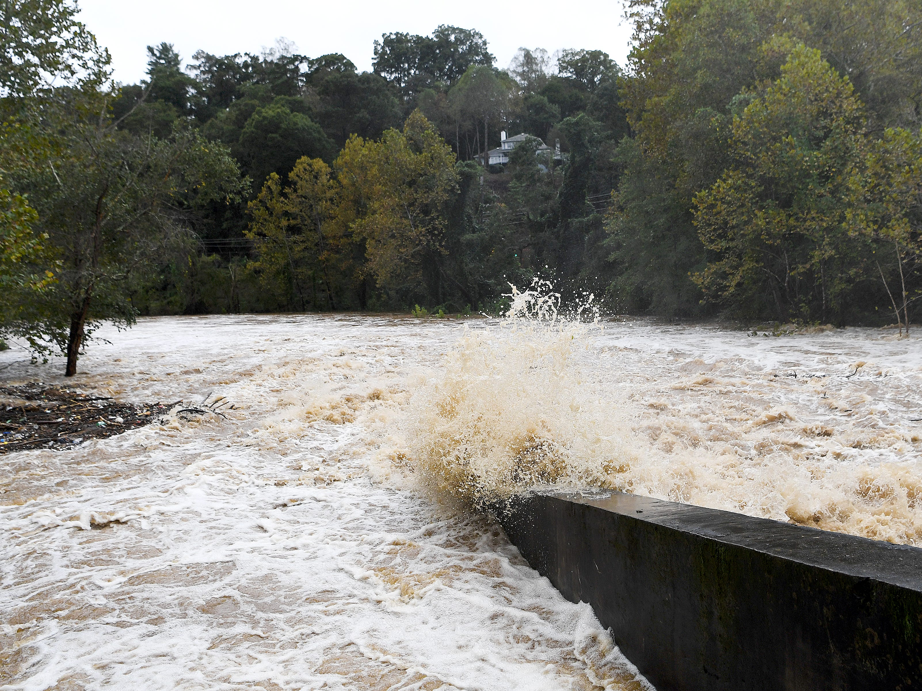 Water surges under Gashes Creek Road as the Swannanoa River floods due to rains from Hurricane Michael on Oct. 11, 2018.