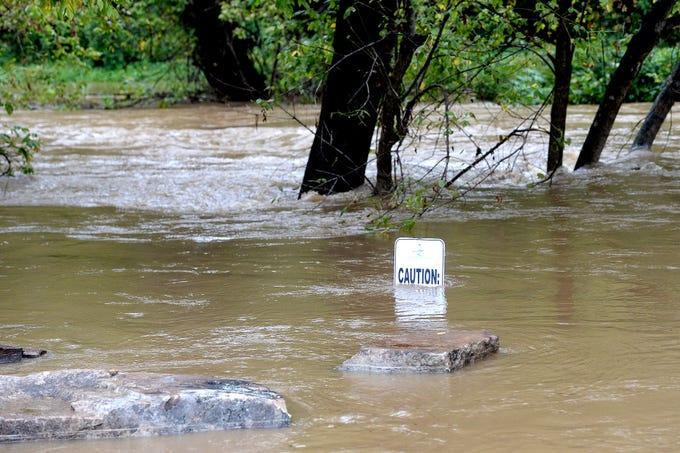The Swannanoa River jumps its banks flooding Swannanoa River Road and reaching toward Thompson Street on Oct. 11, 2018.