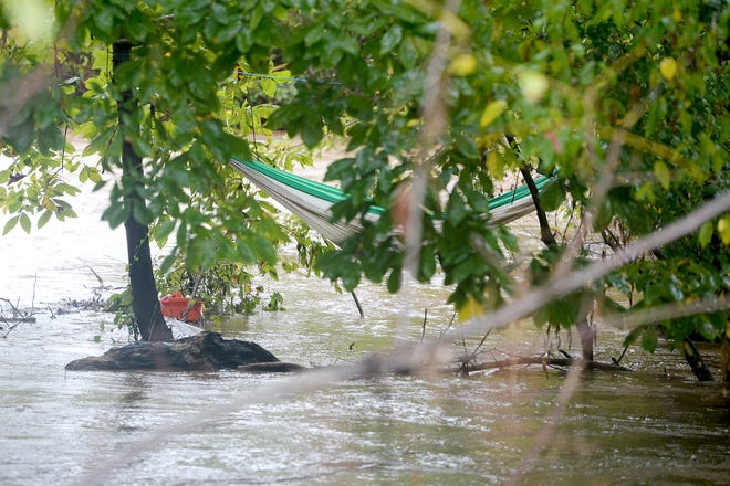 A man and a woman were rescued from a hammock by the Asheville Fire Department as swiftly moving water surrounded them in a makeshift camp along the banks of the Swannanoa River on Oct. 11, 2018.