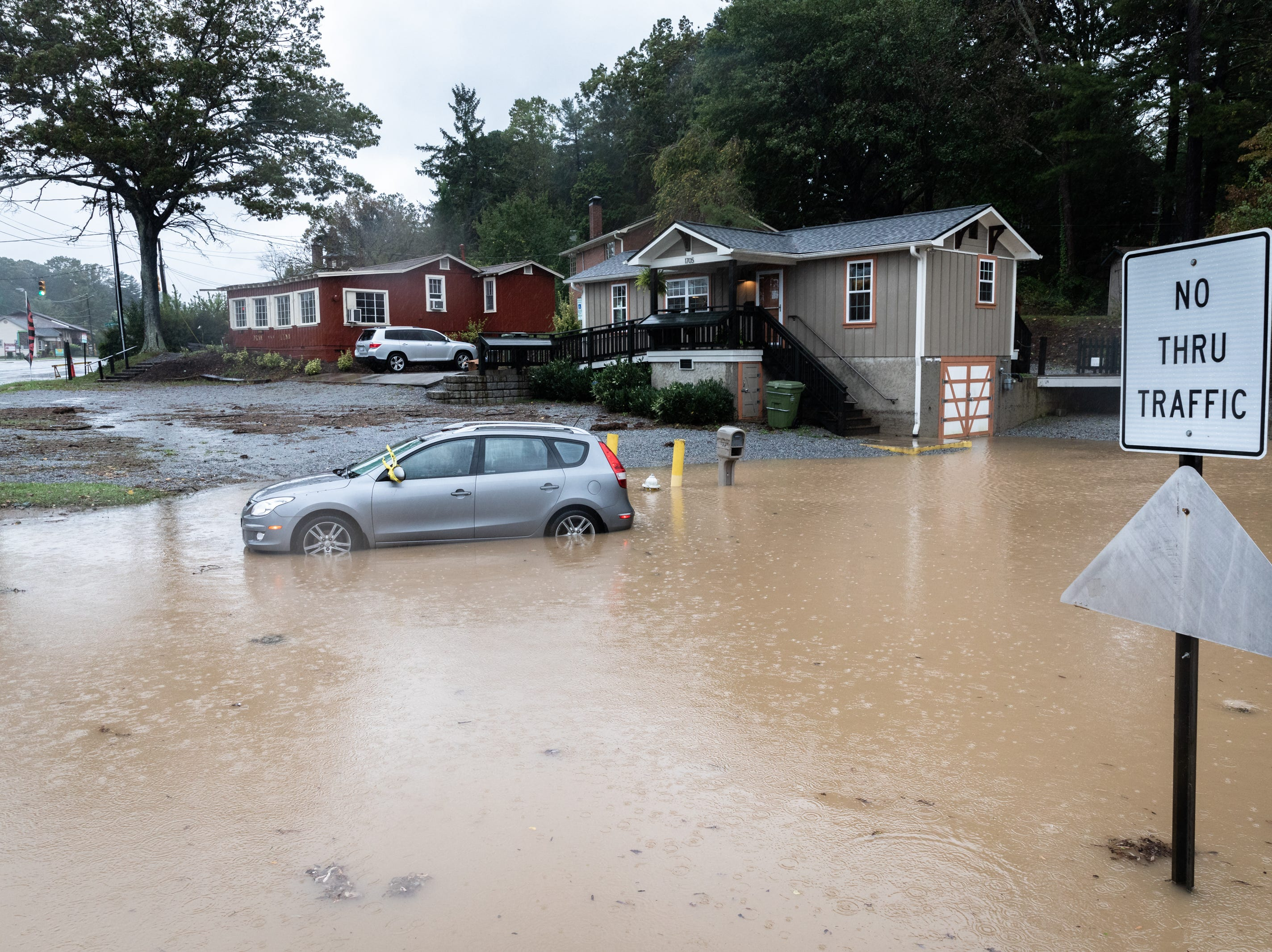 A car sits stranded in floodwaters on Meadowbrook Terrace off of Asheville Highway in Hendersonville Oct. 11, 2018.