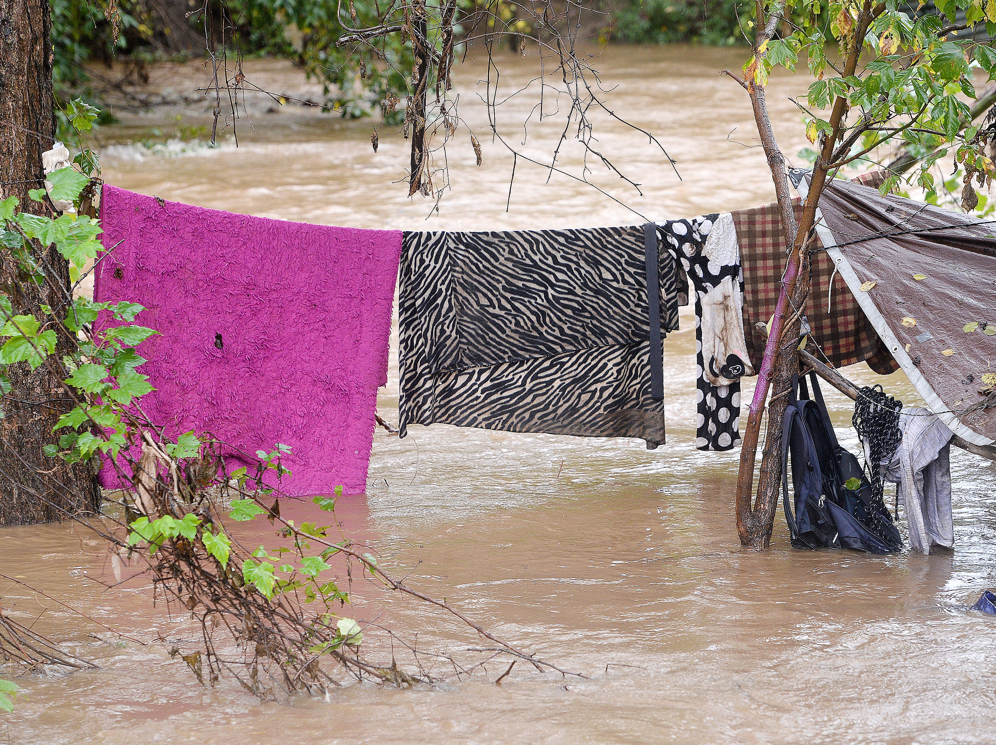 A makeshift camp along the banks of the Swannanoa River is covered in water as the river swells with rain from Hurricane Michael on Oct. 11, 2018. A man and a woman at the camp were rescued from a hammock by the Asheville Fire Department as swiftly moving water surrounded them.