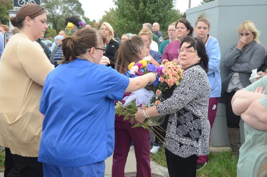 Bonnie Bourque collects flowers in memory of Trish Albrecht at a vigil on Thursday, Oct. 11, 2018 in Battle Creek.