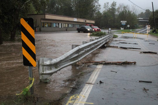 The Swannanoa River spills over Blue Ridge Road as Tropical Storm Michael brings heavy rain to the region on Oct. 11.