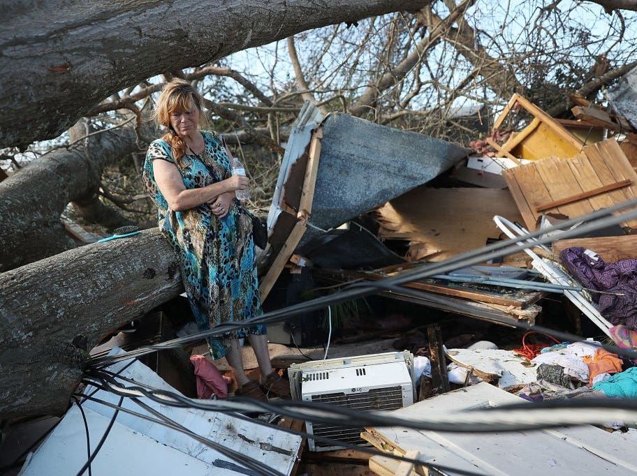 PANAMA CITY, FL - OCTOBER 11:  Kathy Coy stands among what is left of her home after Hurricane Michael destroyed it on October 11, 2018 in Panama City, Florida. She said she was in the home when it was blown apart and is thankful to be alive. The hurricane hit the Florida Panhandle as a category 4 storm.  (Photo by Joe Raedle/Getty Images)