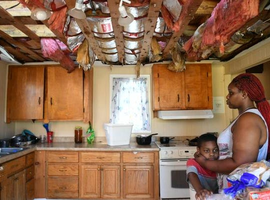 Sheila Dukes hugs her son Ezekiel, 8 as she stands in the ruined kitchen of her rental house in Panama City, FL. Hurricane Michael tore the roof off, flooding the entire wooden structure.