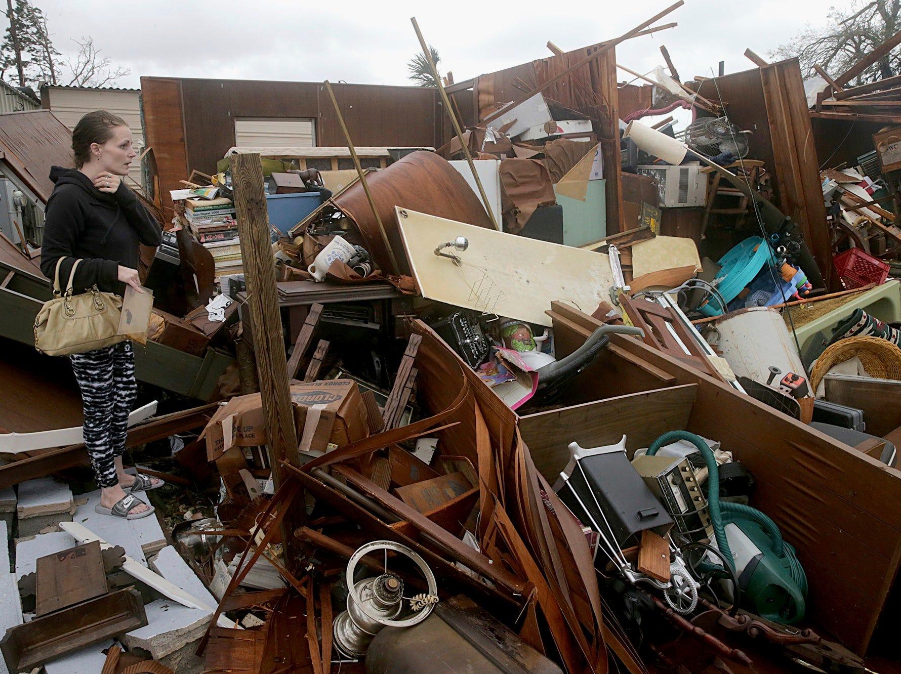 Haley Nelson inspects damages to her family properties in the Panama City, Fla., spring field area after Hurricane Michael made landfall in Florida's Panhandle on Wednesday, Oct. 10, 2018. Supercharged by abnormally warm waters in the Gulf of Mexico, Hurricane Michael slammed into the Florida Panhandle with terrifying winds of 155 mph Wednesday, splintering homes and submerging neighborhoods before continuing its march inland. (Pedro Portal/Miami Herald via AP)