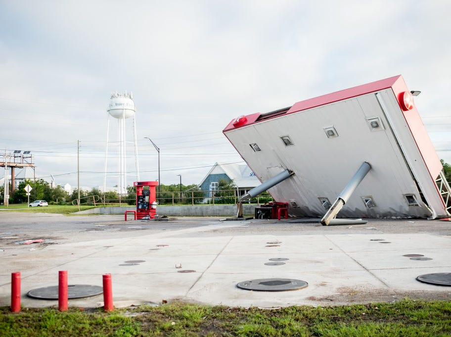 The overhang of a gas station is toppled over in the aftermath of Hurricane Michael on October 11, 2018 in  Inlet Beach, Florida. - Residents of the Florida Panhandle woke to scenes of devastation Thursday after Michael tore a path through the coastal region as a powerful hurricane that killed at least two people. (Photo by Emily KASK / AFP)        (Photo credit should read EMILY KASK/AFP/Getty Images)