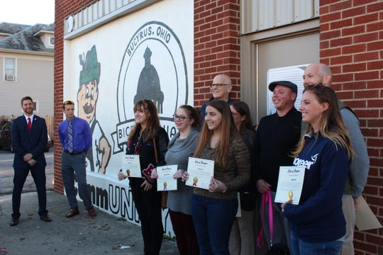 Students and teachers from Bucyrus, Colonel Crawford and Wynford pose for a photo with Bucyrus Mayor Jeff Reser in front of the city's Community Unity mural Thursday, Oct. 11, 2018. Art teachers and students from the three districts designed and painted the mural.