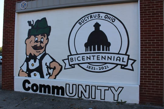 One half of the Community Unity mural includes the logo for the Bucyrus bicentennial and Brattie, the logo for the Bucyrus Bratwurst Festival. Art teachers and students from Bucyrus, Colonel Crawford and Wynford designed and painted the mural.