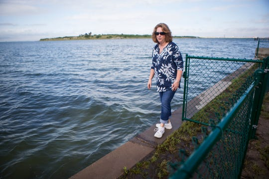 Michelle Morlan walks around examining water on her property that is washed up by passing boats on Oct. 10, 2018 in Ingleside.