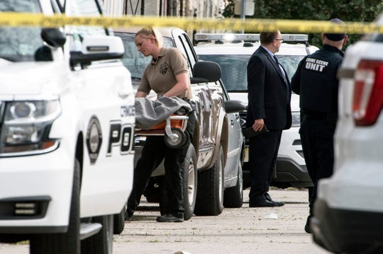 Officials on Thursday remove a child's body found in an alley on the 800 block of Mount Ephraim Avenue in Camden.