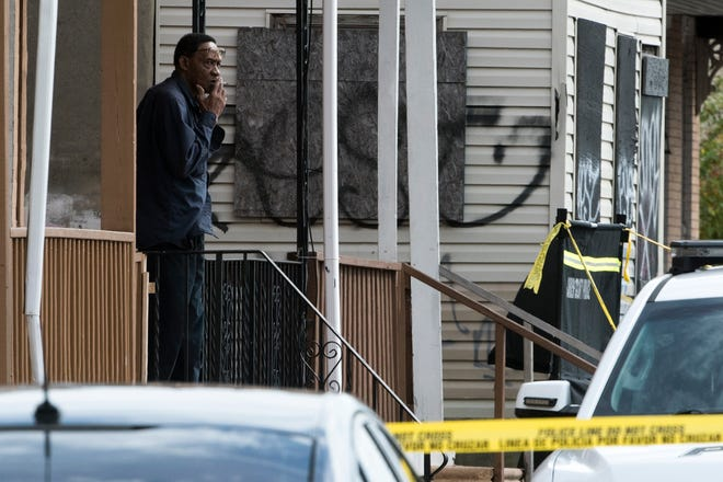 A neighbor watches Thursday as officials remove suspected human remains found in an alley on the 800 block of Mount Ephraim Avenue in Camden.