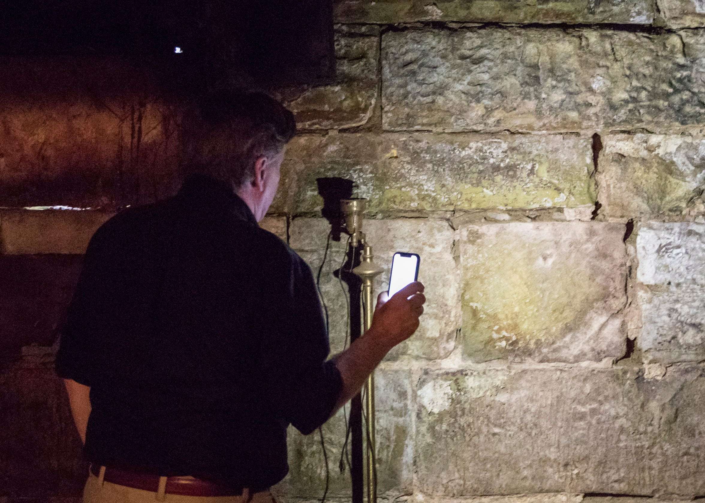 Robert Loversidge, architect and CEO of Schooley Caldwell, shines a light on the sandstone blocks that make up the foundation of the old canal warehouse on the corner of Mulberry and East Main streets.