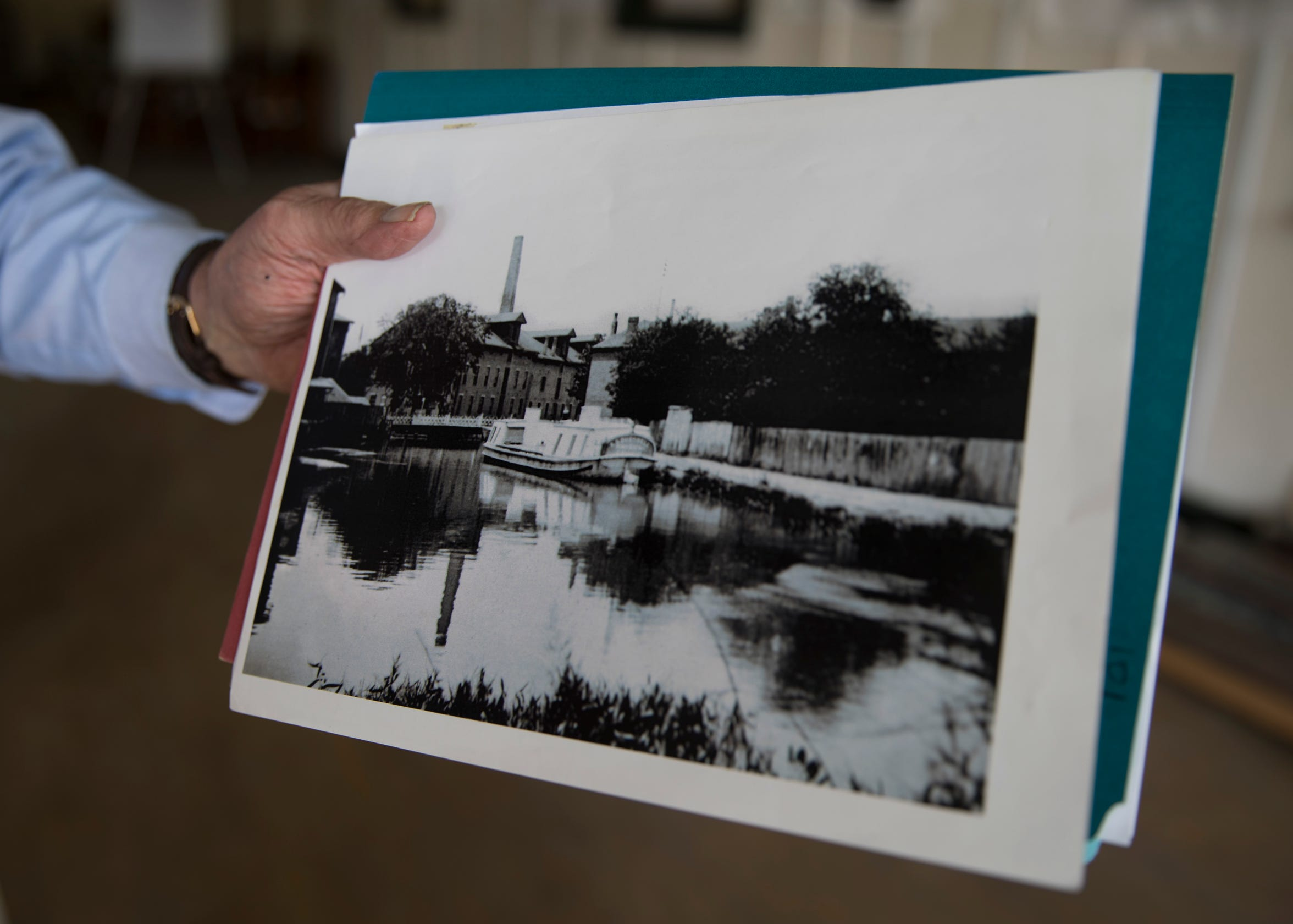 Franklin Conaway holds a photo of the old canal warehouse taken in the late 1800s when the canal was still active in Chillicothe.