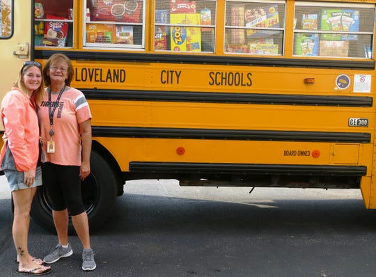 "Loveland school bus driver Lisa Simpson, right, who had the idea to ""Stuff-a-Bus"" for the LIFE Food Pantry, stands in front of the stuffed bus with her daughter Michelle Winter."