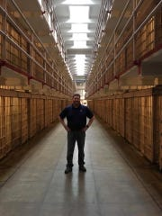 "Andrew Lange, production manager at, Stewart Iron Works, stands in the middle of ""Broadway,"" the nickname for the main cell block at Alcatraz Island. The company put brass iron patent ID plates back up at the infamous San Francisco prison in October 2018."
