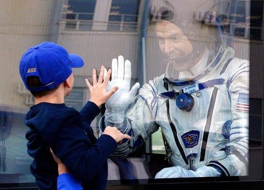 U.S. astronaut Nick Hague, member of the main crew to the International Space Station (ISS), waves to his son from a bus prior to the launch of Soyuz-FG rocket at the Russian leased Baikonur cosmodrome, Kazakhstan, Thursday, Oct. 11, 2018. (AP Photo/Dmitri Lovetsky, Pool)