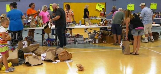 """Lots of volunteers were on hand to unpack, sort and even repack the nearly 1,000 food items donated by Loveland Schools' """"Stuff-a-Bus"""" food drive for LIFE Food Pantry."""