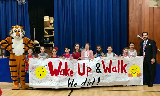 Tamaques mascot Tammi the Tiger joins principal David Duelks and students as they hold up a banner signed by all those who walked to school on Oct. 3.