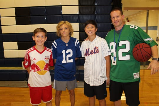 """Middle School students, Robbie Battiste, Brian Edelman and Colin Chou take a moment to pose for a picture with Sean Mealey, WMS Physical Education Teacher during the """"Week of Respect""""."""