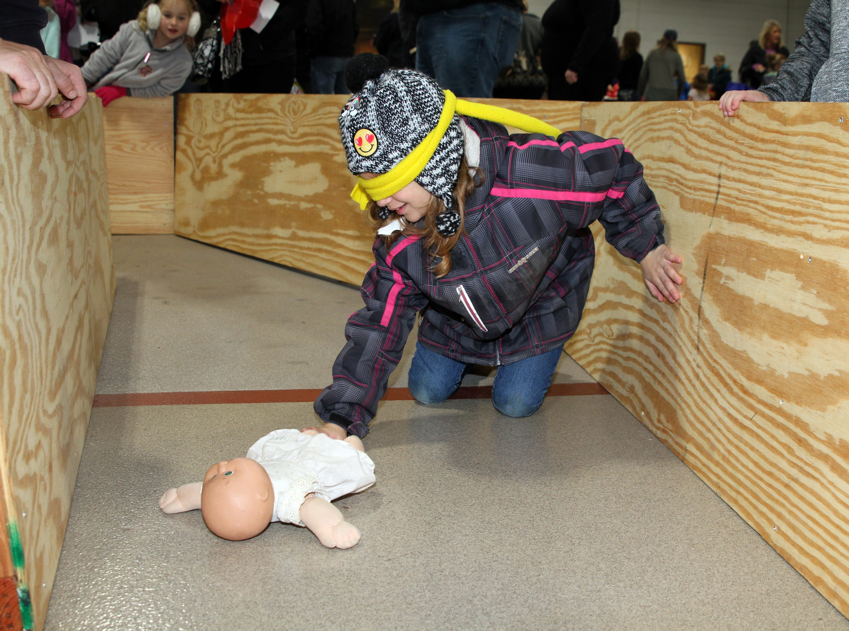 Landyn Parsons, 8, of Huxley stays low and finds the baby doll in the simulated smoke-filled dark hallway during the Ankeny Fire Department's Fire Prevention Week Open House on Wednesday, Oct. 10, 2018 at Fire Station #1, 120 N.W. Ash Dr in Ankeny.