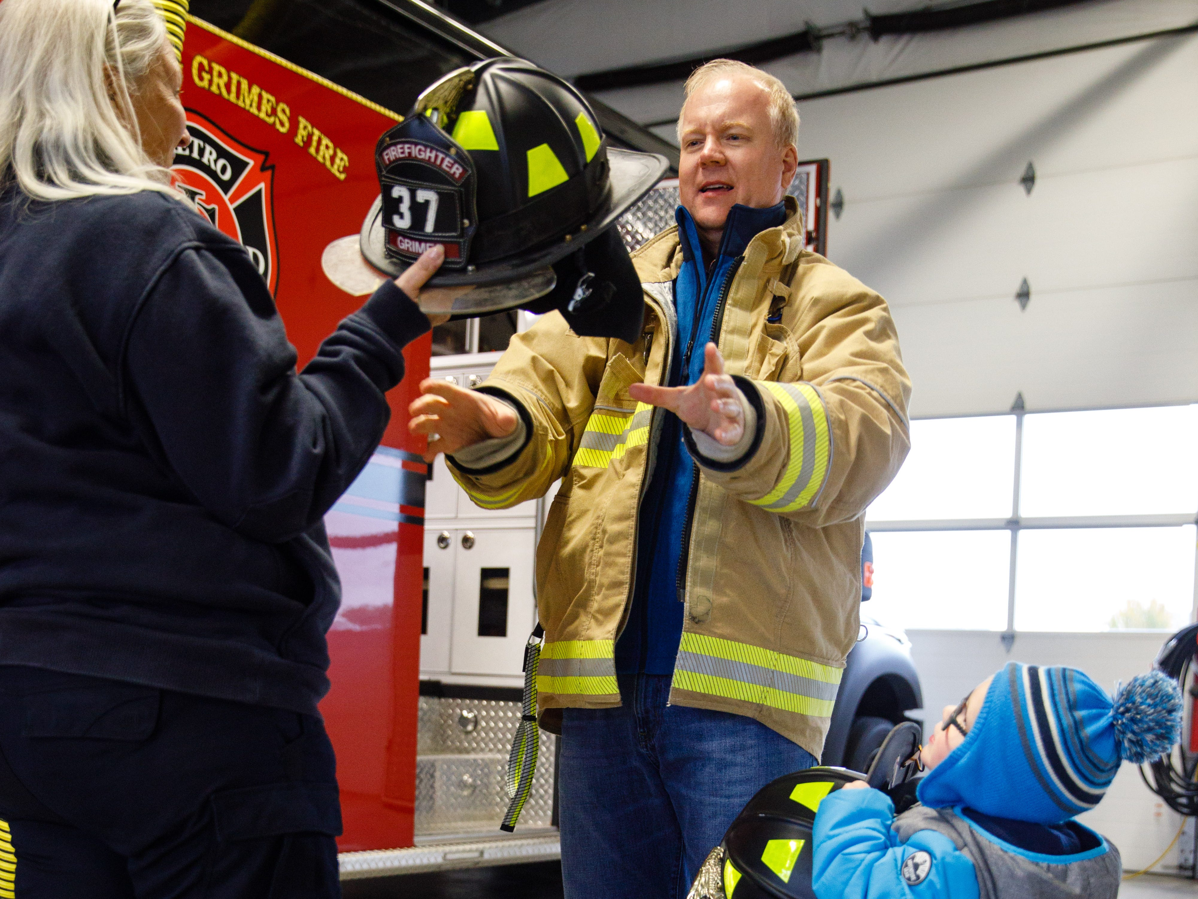 Jason Lems of Johnston tries on firefighting protective equipment with the help of Braxton Lems, 3, and EMT/Firefighter Gail Thompson Wednesday, Oct. 10, 2018, during the Johnston-Grimes Metropolitan Fire Department's annual Fire Prevention Week Open House at the 62nd Avenue Fire Station in Johnston.