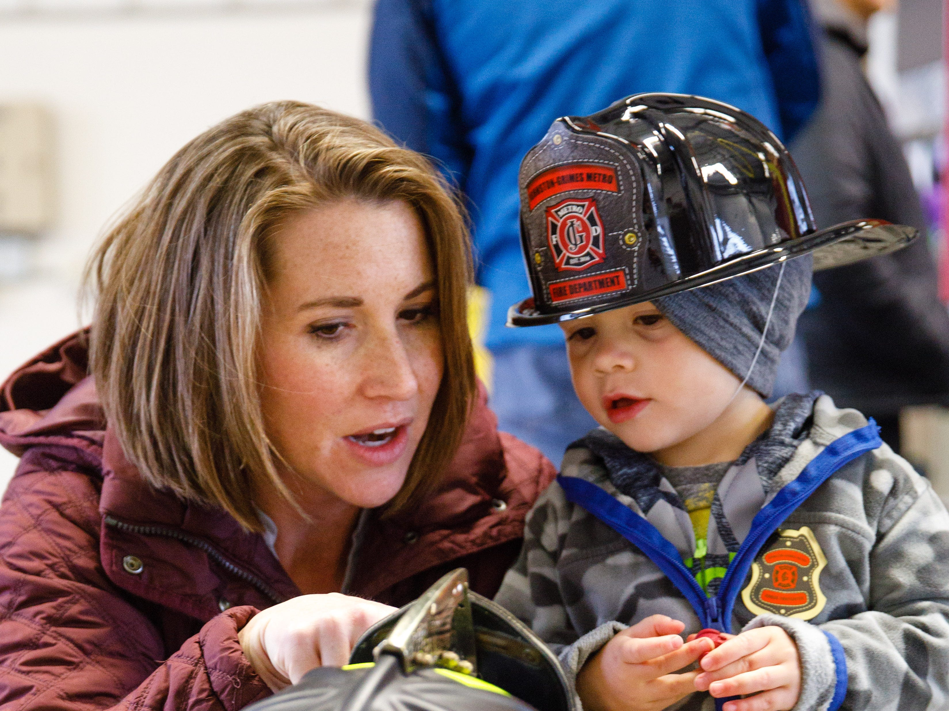 Laura Sprague and TJ Sprague, 2, check out a firefighter helmet Wednesday, Oct. 10, 2018, during the Johnston-Grimes Metropolitan Fire Department's annual Fire Prevention Week Open House at the 62nd Avenue Fire Station in Johnston.