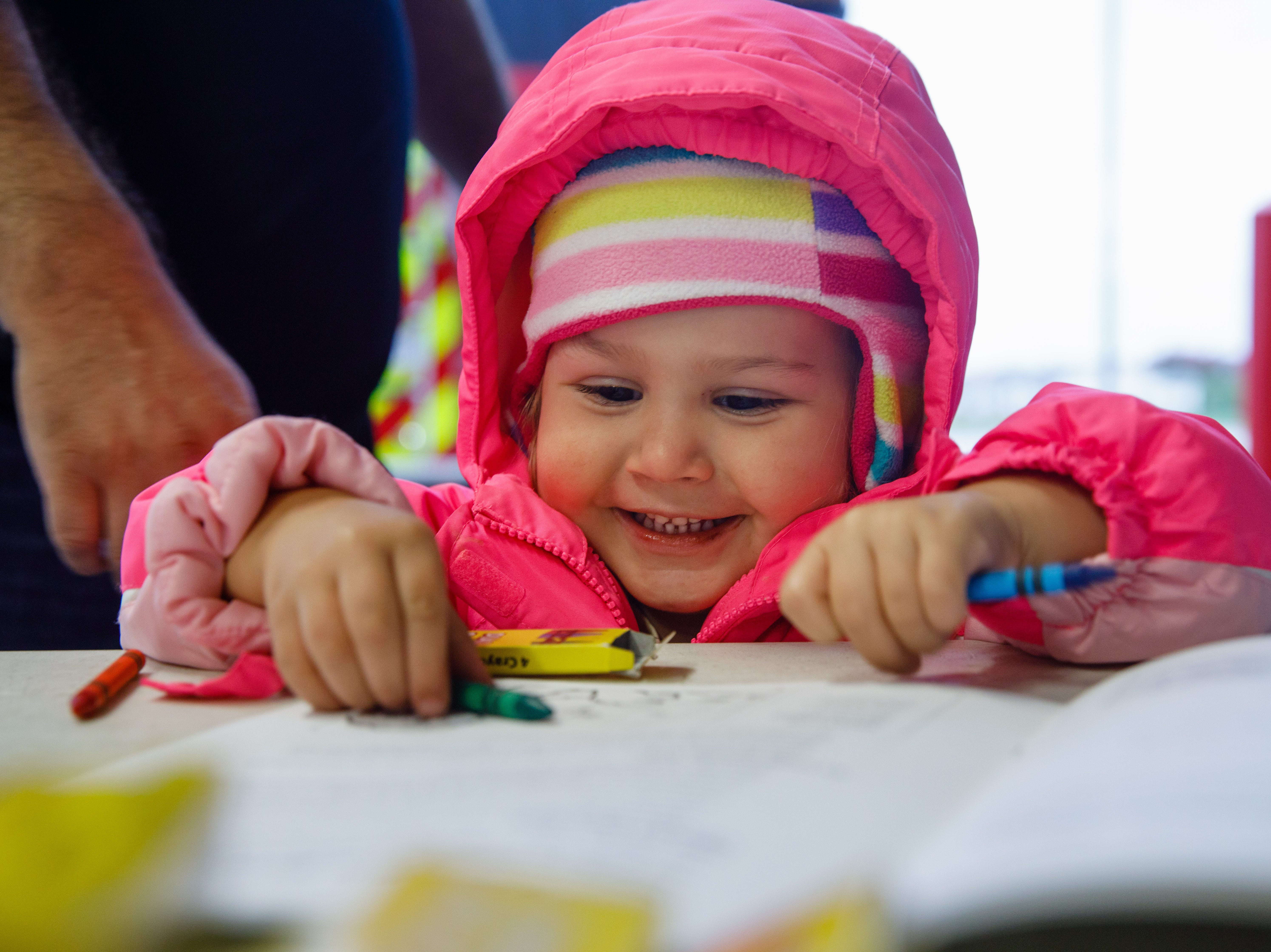 Aubree Albizures, 2, opens a coloring book Wednesday, Oct. 10, 2018, during the Johnston-Grimes Metropolitan Fire Department's annual Fire Prevention Week Open House at the 62nd Avenue Fire Station in Johnston.