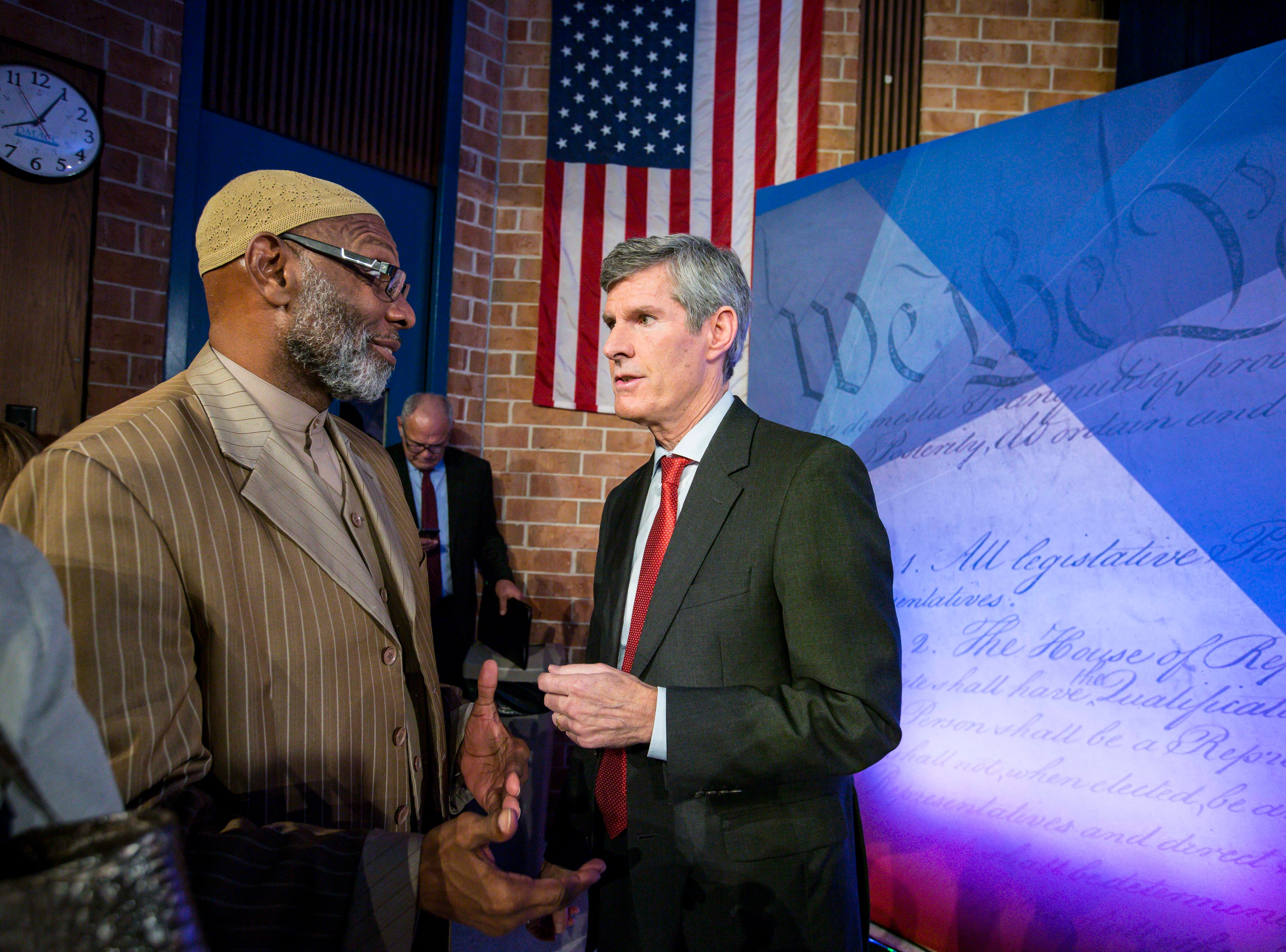 Democratic challenger Fred Hubbell talks with Ako Abdul-Samad after the debate Wednesday, Oct. 10, 2018, at Des Moines Area Community College in Ankeny, Iowa.