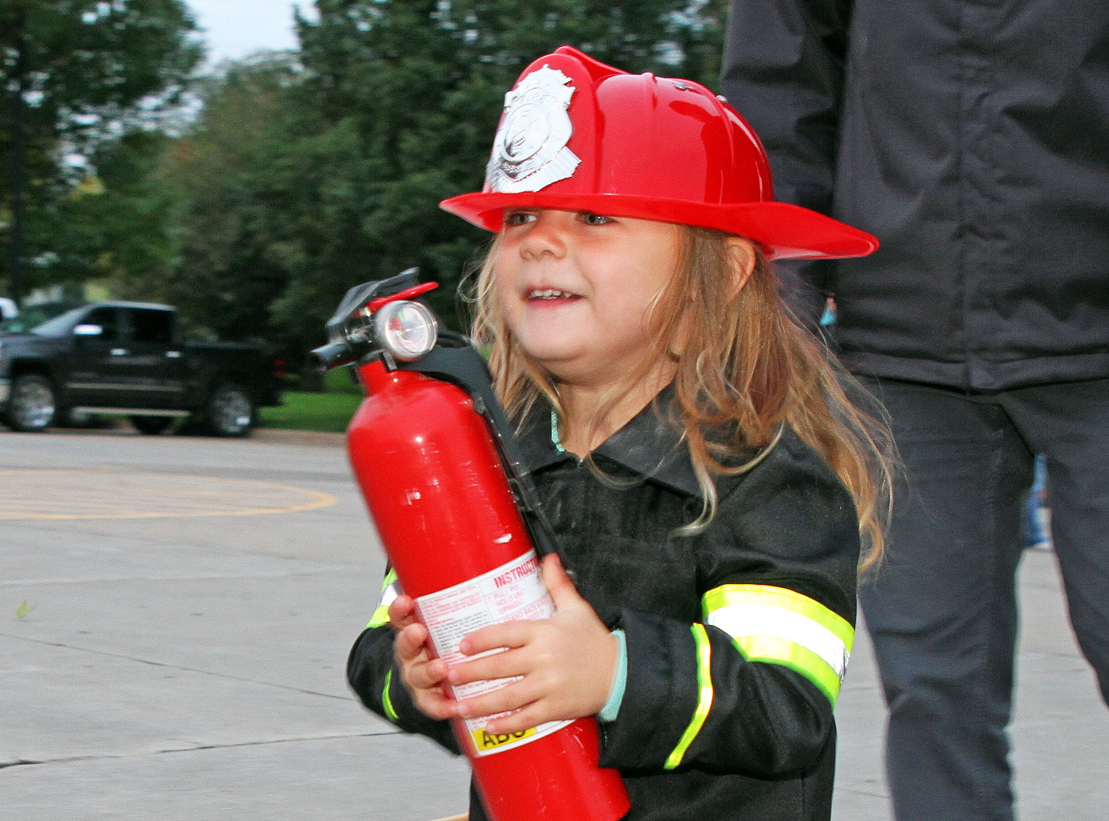 Adelyn Gervais, 3, of Ankeny carries a fire extinguisher at the Kids' Firefighter Challenge during the Ankeny Fire Department's Fire Prevention Week Open House on Wednesday, Oct. 10, 2018 at Fire Station #1, 120 N.W. Ash Dr. in Ankeny.