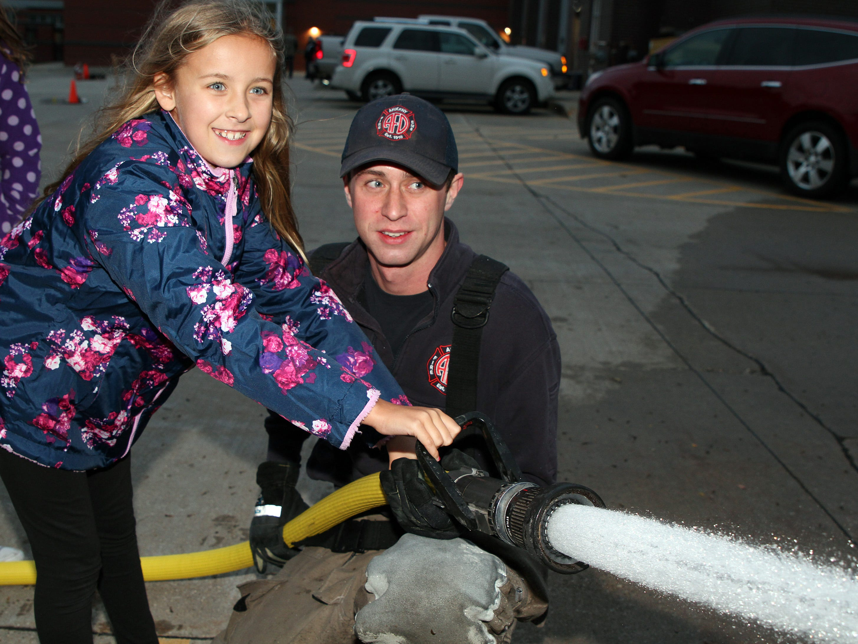 Madi Bachman, 10, learns how to spray water on the target from Ankeny Firefighter Cole White during the Ankeny Fire Department's Fire Prevention Week Open House on Wednesday,  Oct. 10, 2018 at Fire Station #1, 120 N.W. Ash Dr in Ankeny.