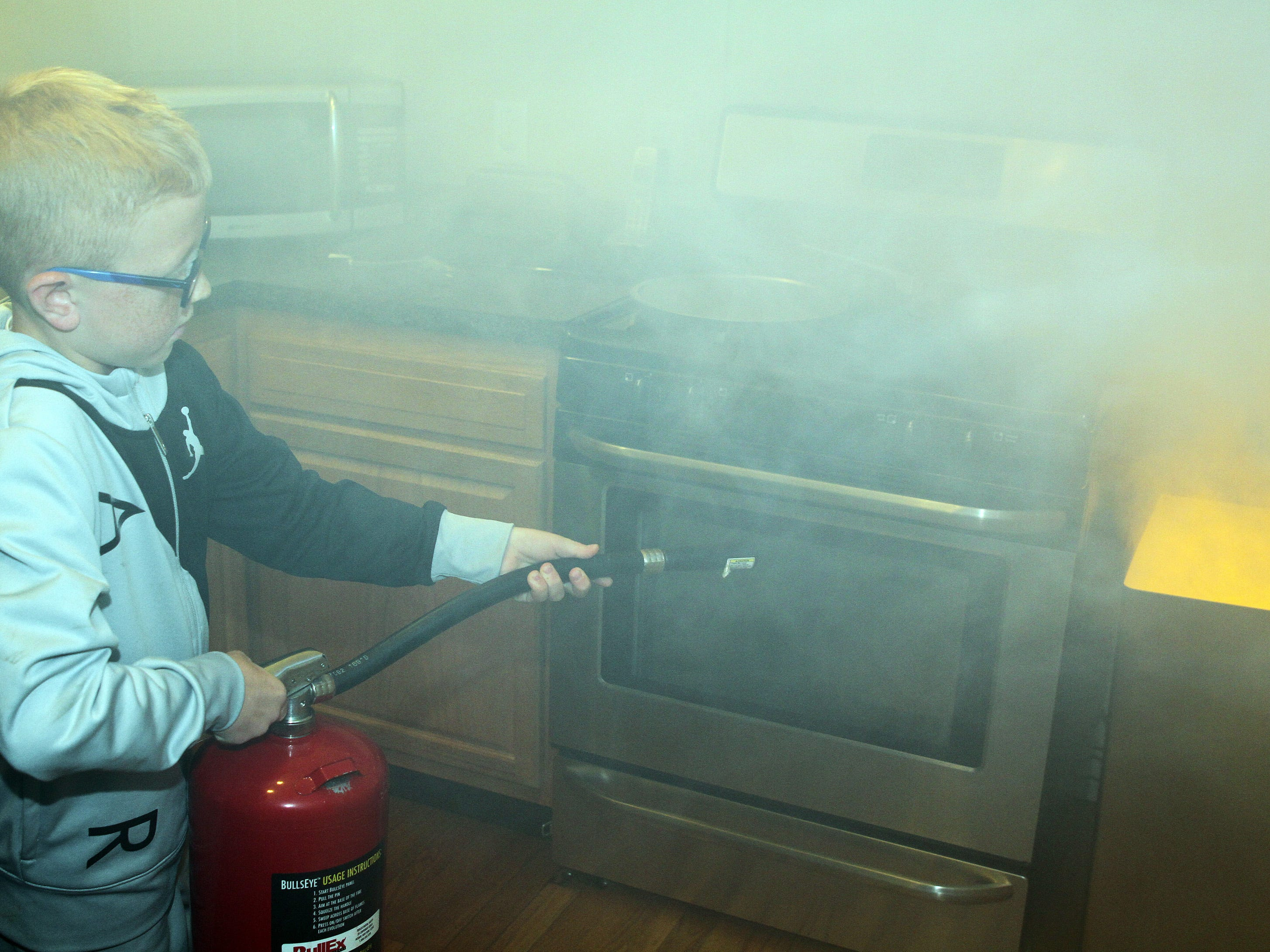 Tate Goche, 8, of Ankeny puts out a kitchen trash can fire in the smoke house during the Ankeny Fire Department's Fire Prevention Week Open House on Wednesday, Oct. 10, 2018 at Fire Station #1, 120 N.W. Ash Dr in Ankeny. The Open House includes a variety of educational, family-oriented hands-on activities for all ages. Residents can learn more about the power of fire prevention and technologies available to protect their own families from fire.
