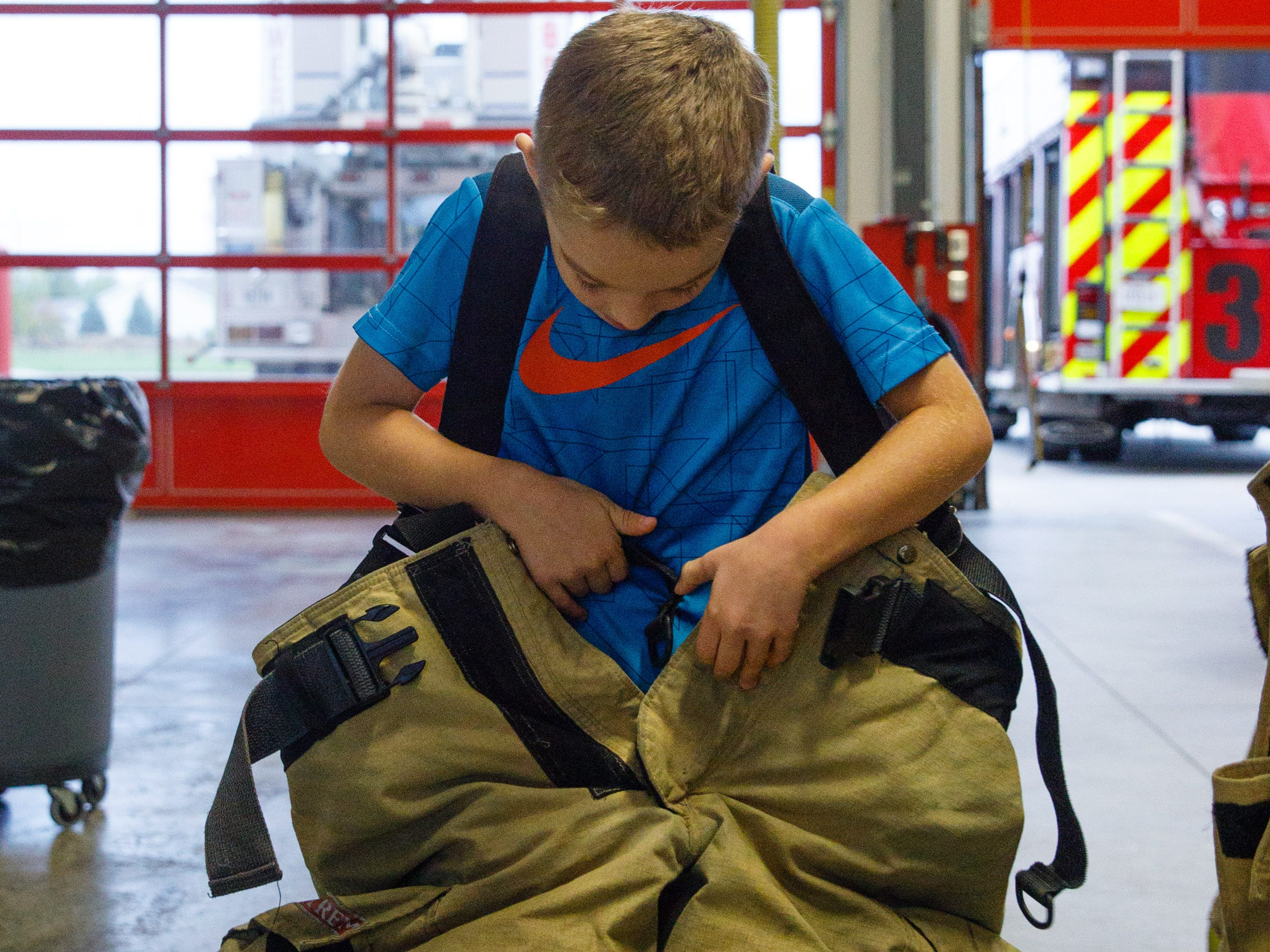 Wyatt Puffer, 6, of Des Moines, tries on firefighter protective equipment Wednesday, Oct. 10, 2018, during the Johnston-Grimes Metropolitan Fire Department's annual Fire Prevention Week Open House at the 62nd Avenue Fire Station in Johnston.